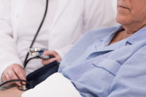 Elderly patient lying in bed and having blood pressure measured