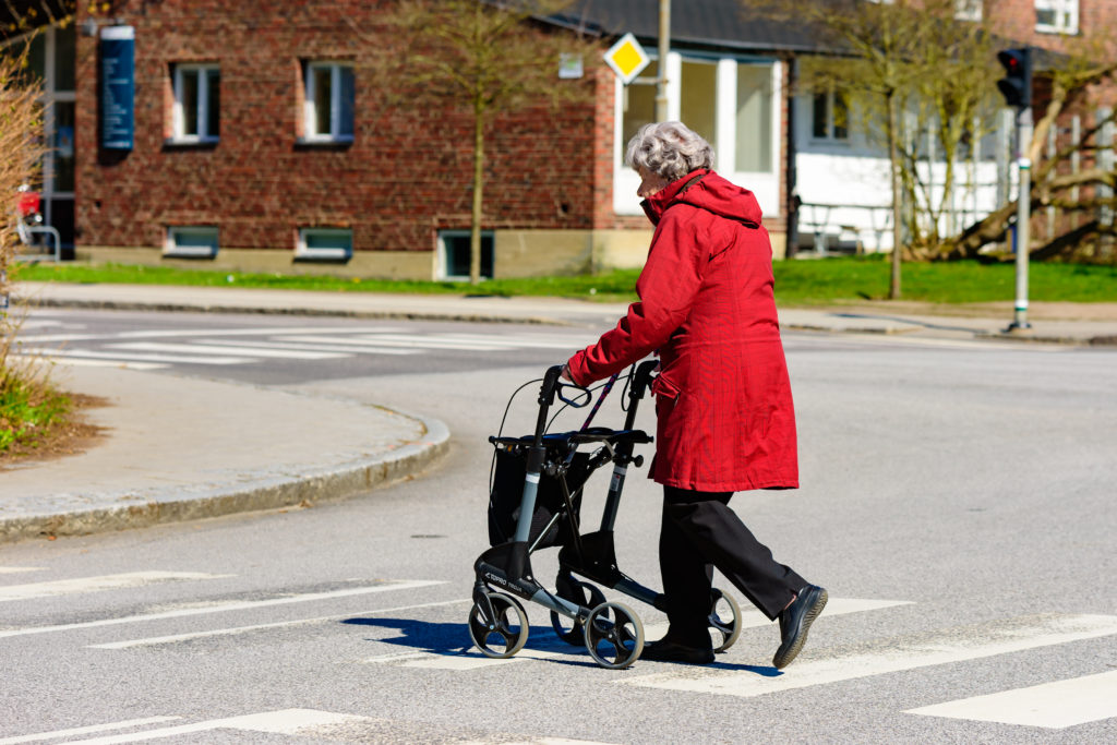 Lund, Sweden - April 11, 2016: Real life in the city. Elderly woman is out walking, crossing a street with her walker. No traffic visible.