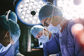 Concentrated female surgeon performing surgery with her team in hospital operating room. Medics during surgery in operation theater.