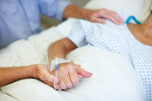 Closeup shot of an elderly man holding his wife's hand while she is ill in the hospital
