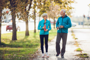 Mature couple walking together with water bottles. Copy space.