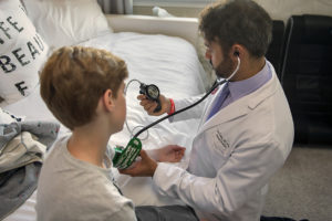 a medical professional takes a young man's blood pressure