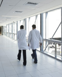 Physicians walking across bridge between two buildings
