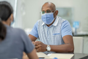 Man wearing mask talking to doctor