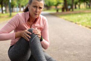 Women holding knee in pain
