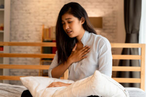Woman sitting on bed with hand to chest as if having trouble breathing